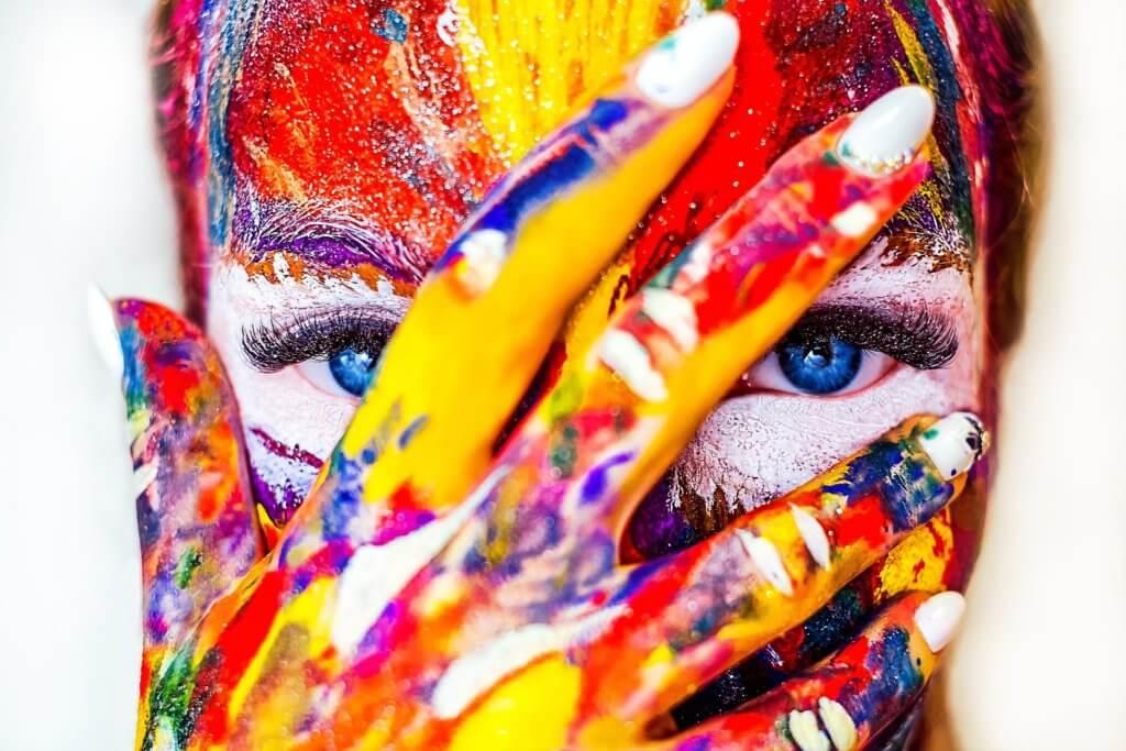 Buntes Frauengesicht mit Hand davor, weiterführendes Coaching Farben